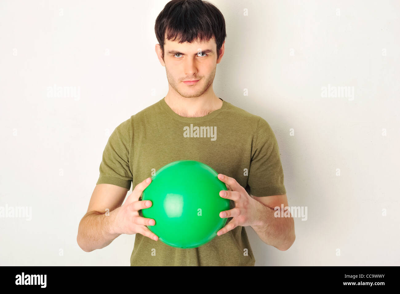 Portrait of handsome man holding green ball in his arms. Standing near the wall at gym - Stock Image