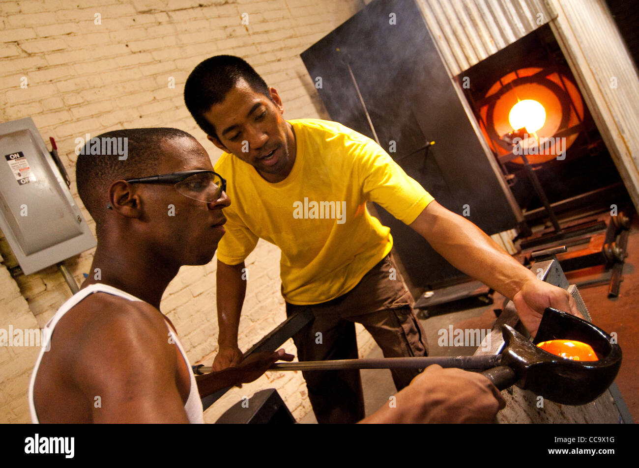 an instructor helps a teen student make glass. Glass Roots, Newark New Jersey, USA - Stock Image
