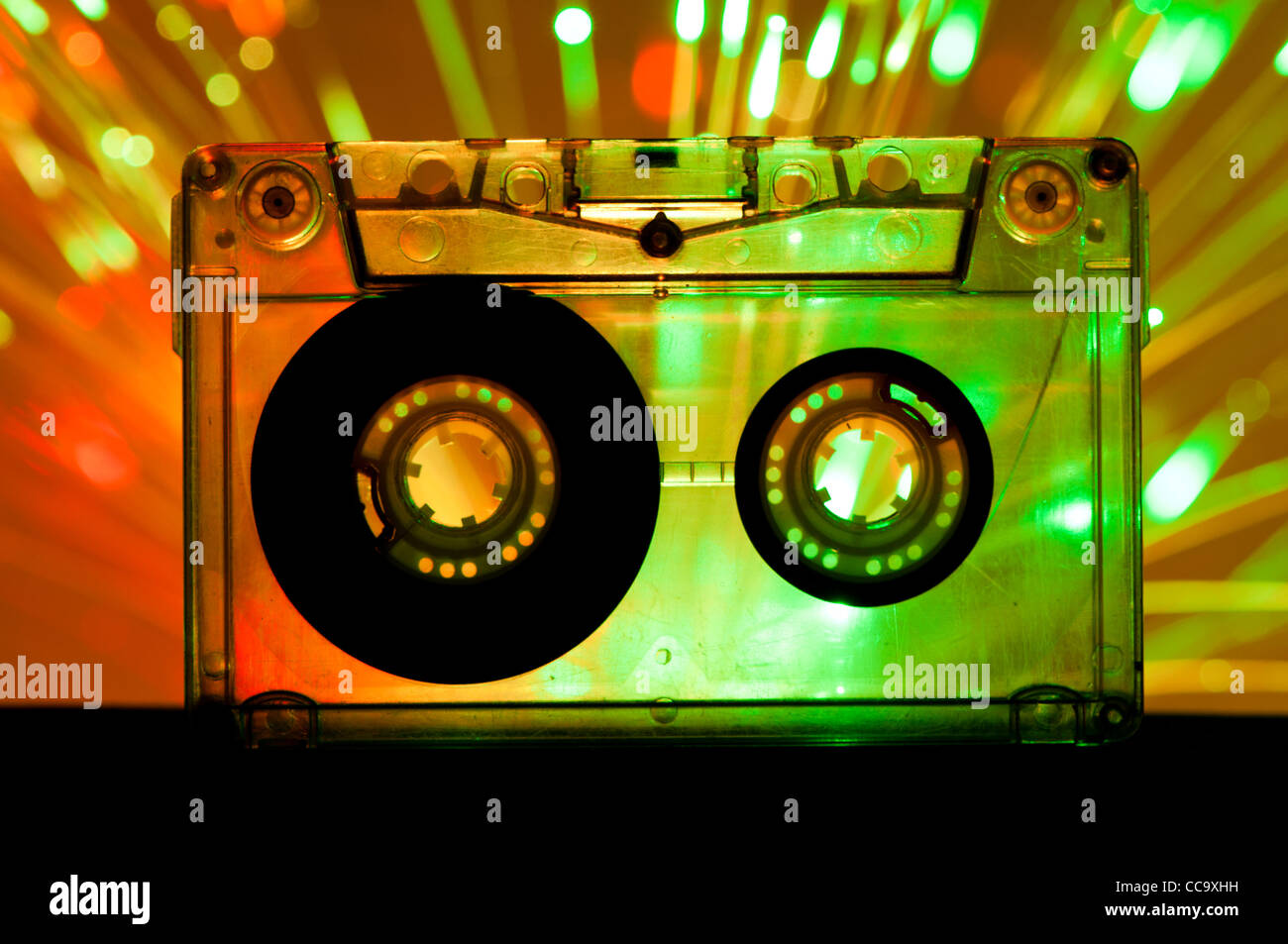 Transparent Cassette tape and green orange color disco lights background - Stock Image