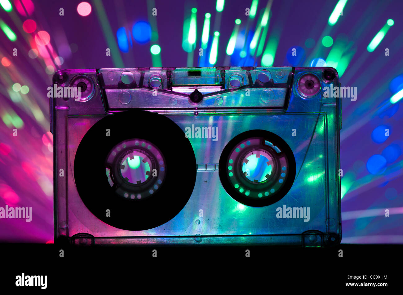 Transparent Cassette tape and blue pink color disco light background - Stock Image