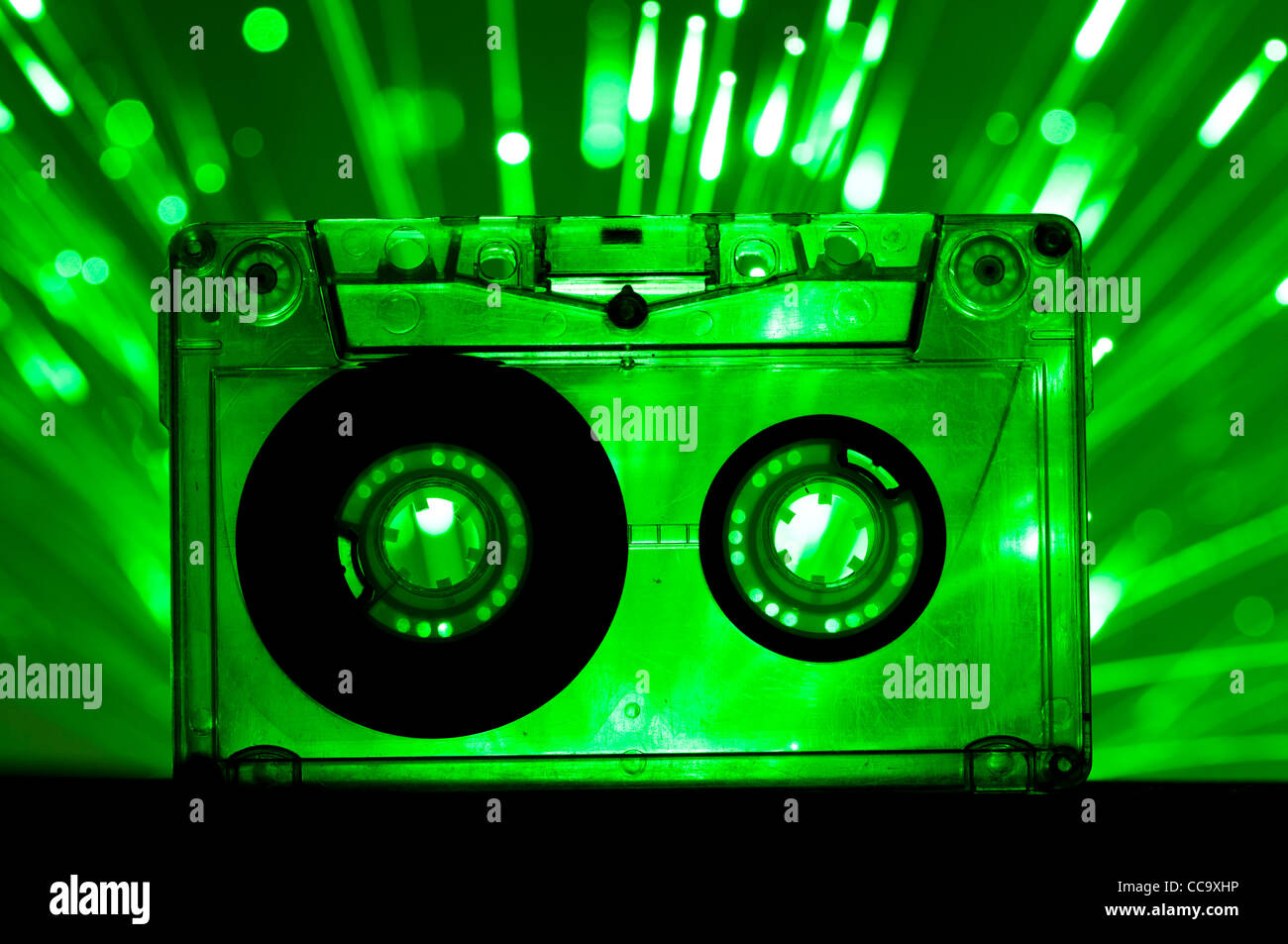 Transparent Cassette tape and green color disco lights background - Stock Image
