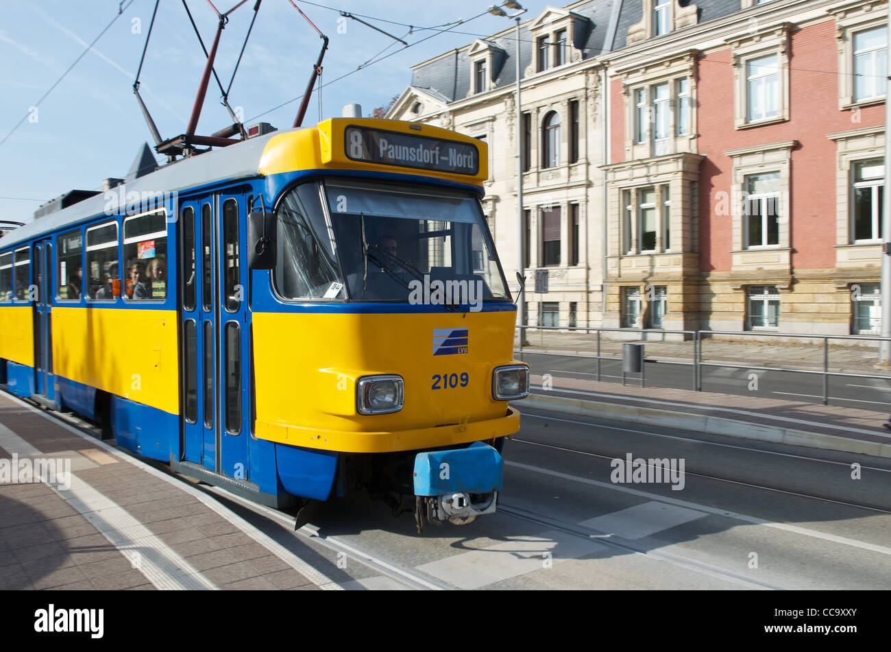 An older style yellow and blue electric tram on the streets of Leipzig in Germany - Stock Image