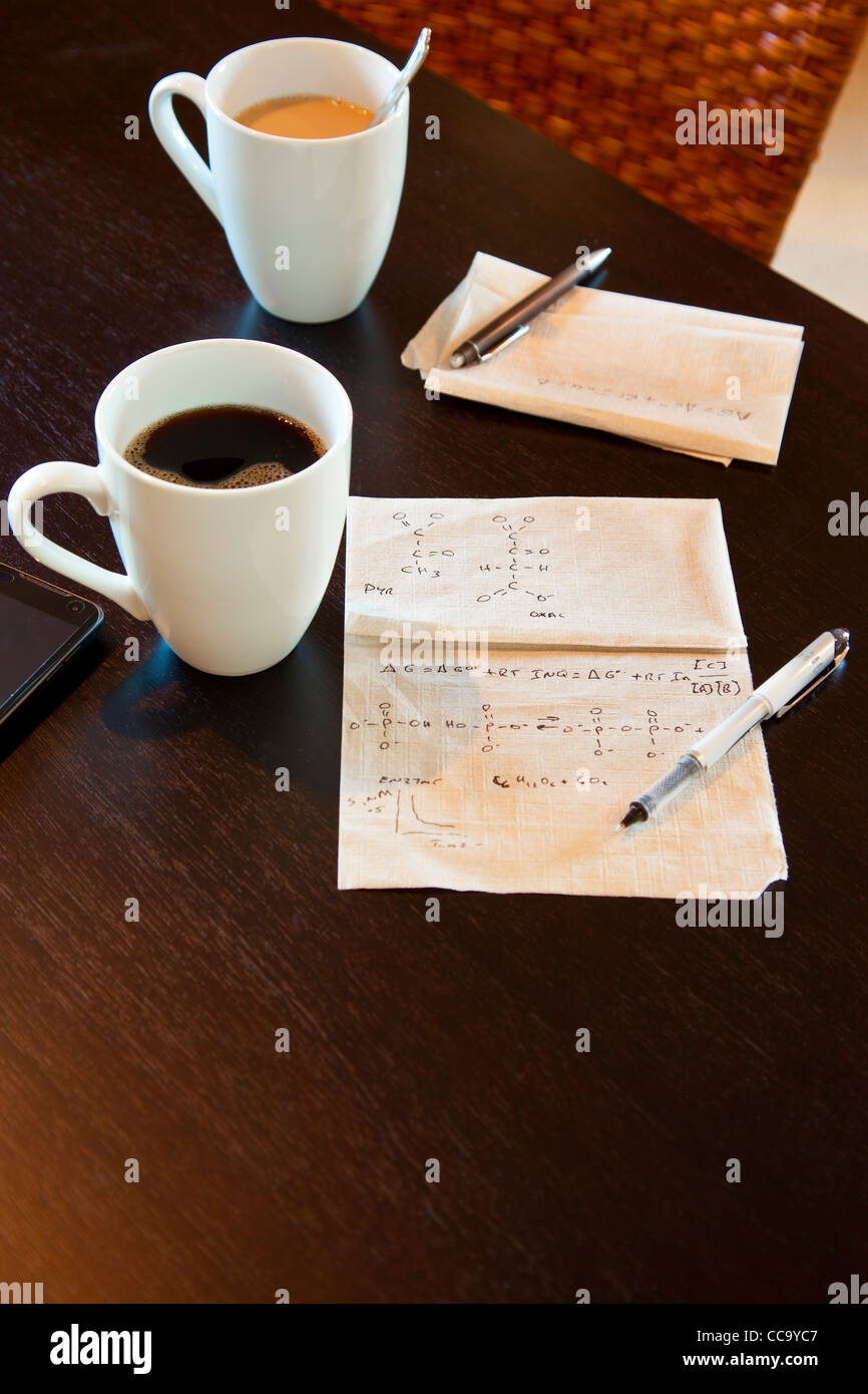 Molecular calculations on a paper napkin on a coffee shop table - Stock Image