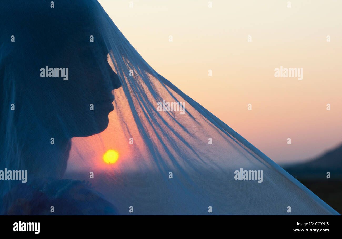 Indian girl and veil at sunset. Silhouette. Andhra Pradesh, India - Stock Image