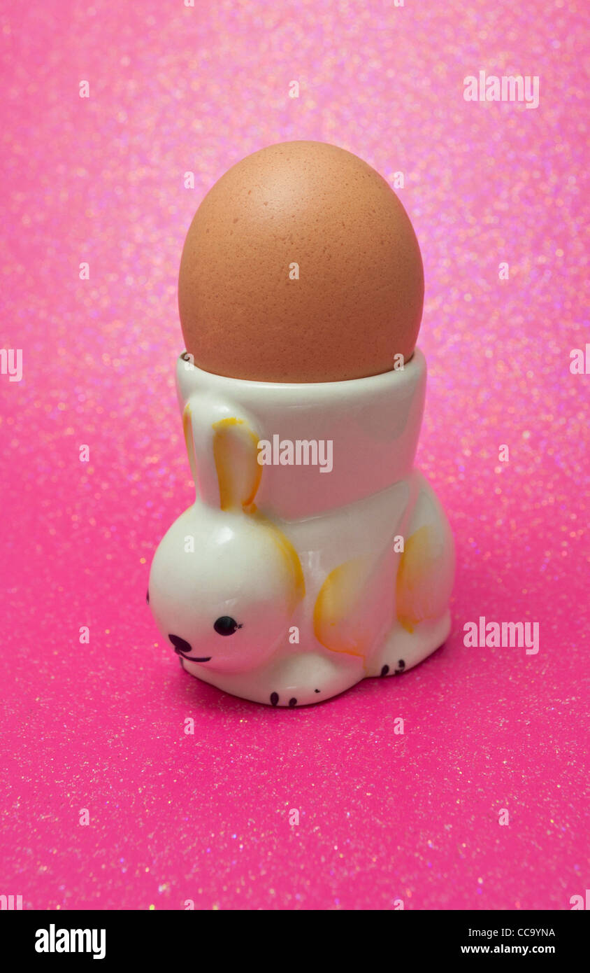 Hen's egg in a vintage novelty egg cup in the shape of a rabbit Stock Photo