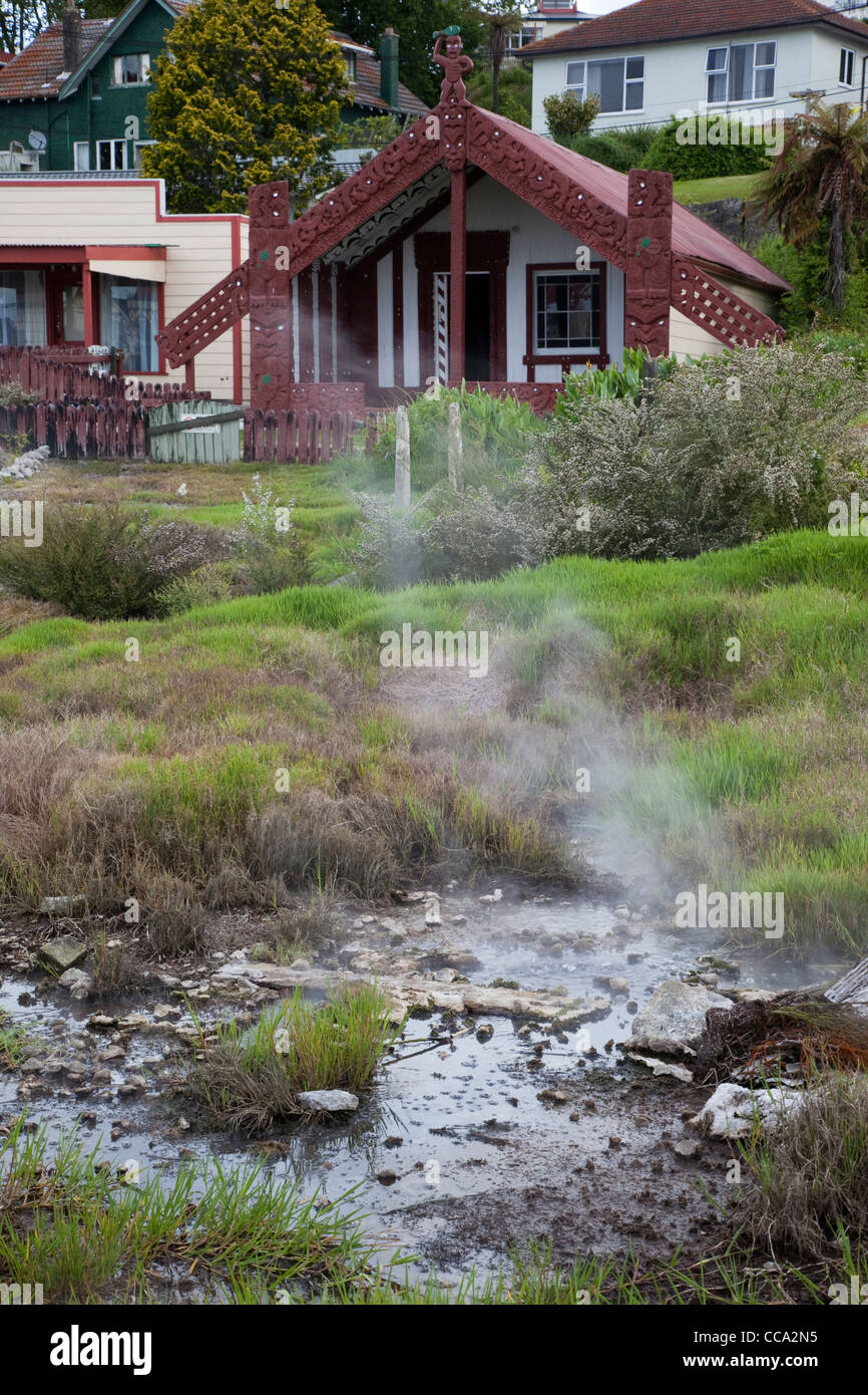 Ohinemutu Village, Rotorua, New Zealand. Thermal Spring in front yard of village house built in traditional style. - Stock Image