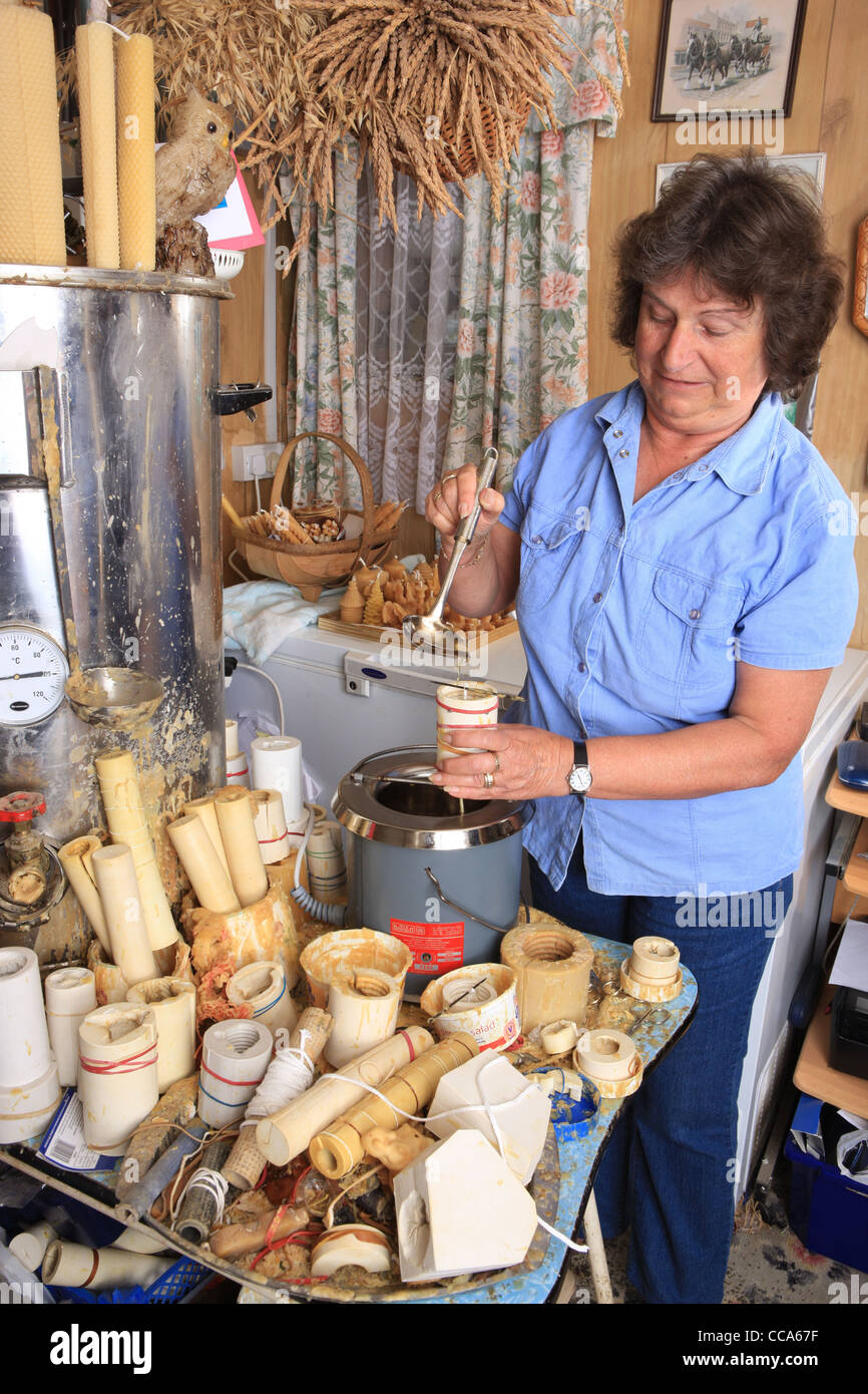 Enid Chubb  making candles by pouring  hot Beeswax into a mould with a ladle - Stock Image