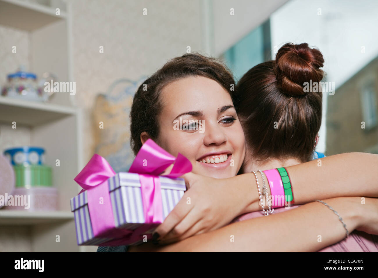Young women holding birthday gift and embracing - Stock Image