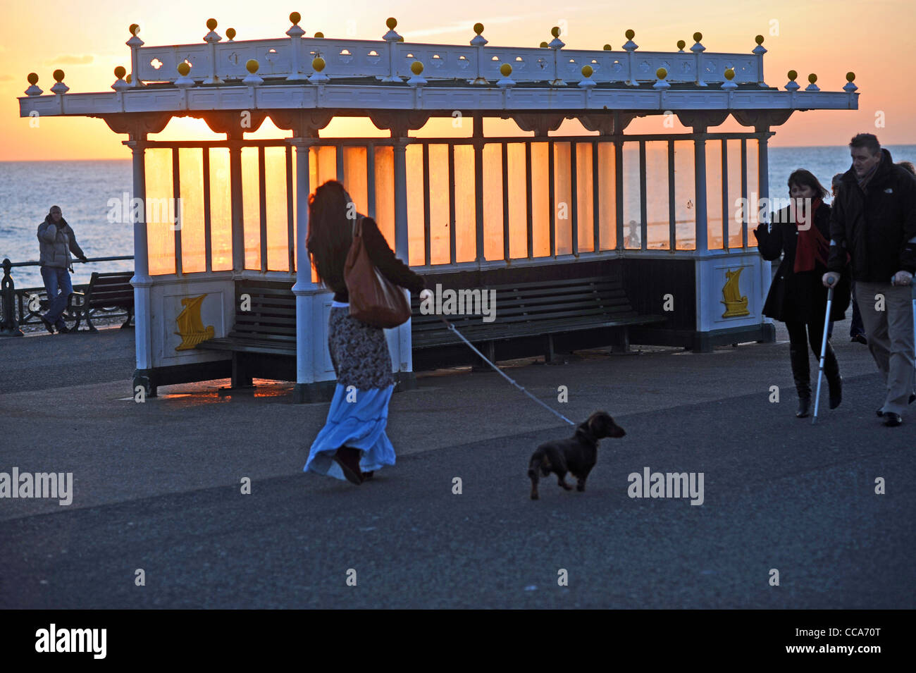 People out walking past a shelter during a spectacular sunset along Hove seafront Sussex UK Stock Photo