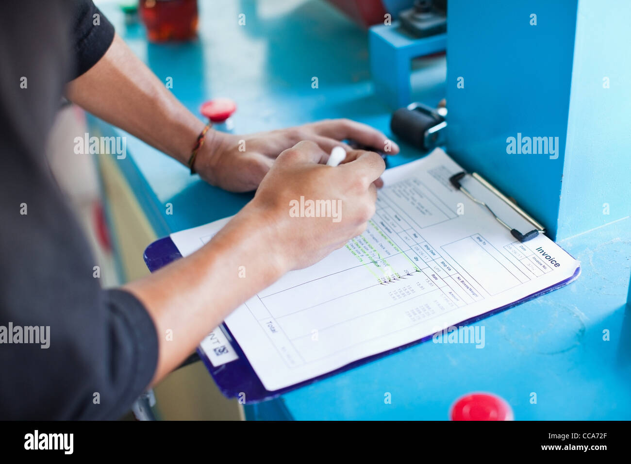 Man checking off items on an invoice - Stock Image
