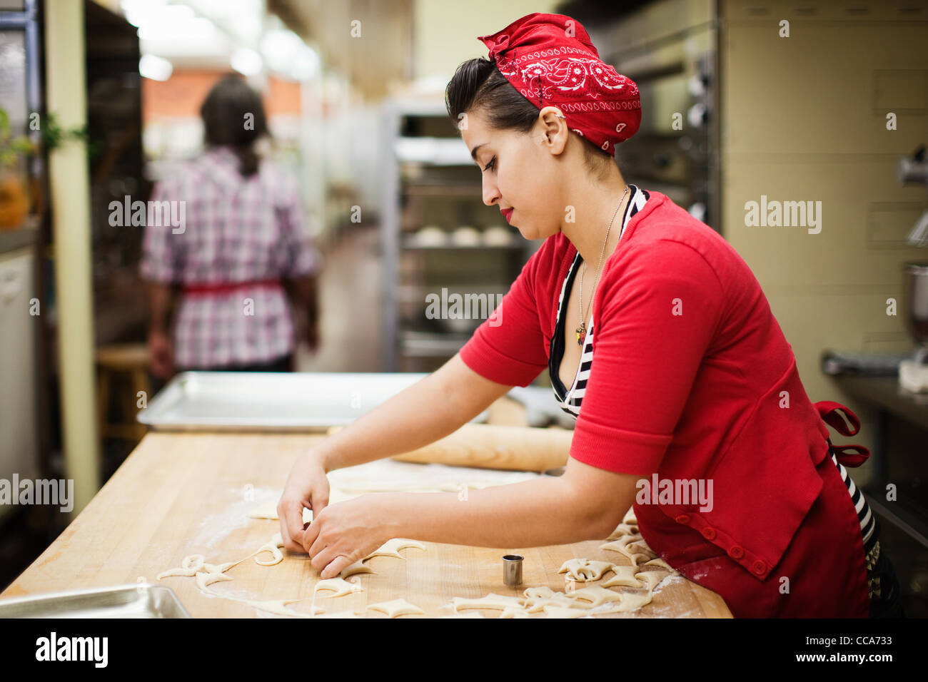 Young baker preparing food in kitchen - Stock Image