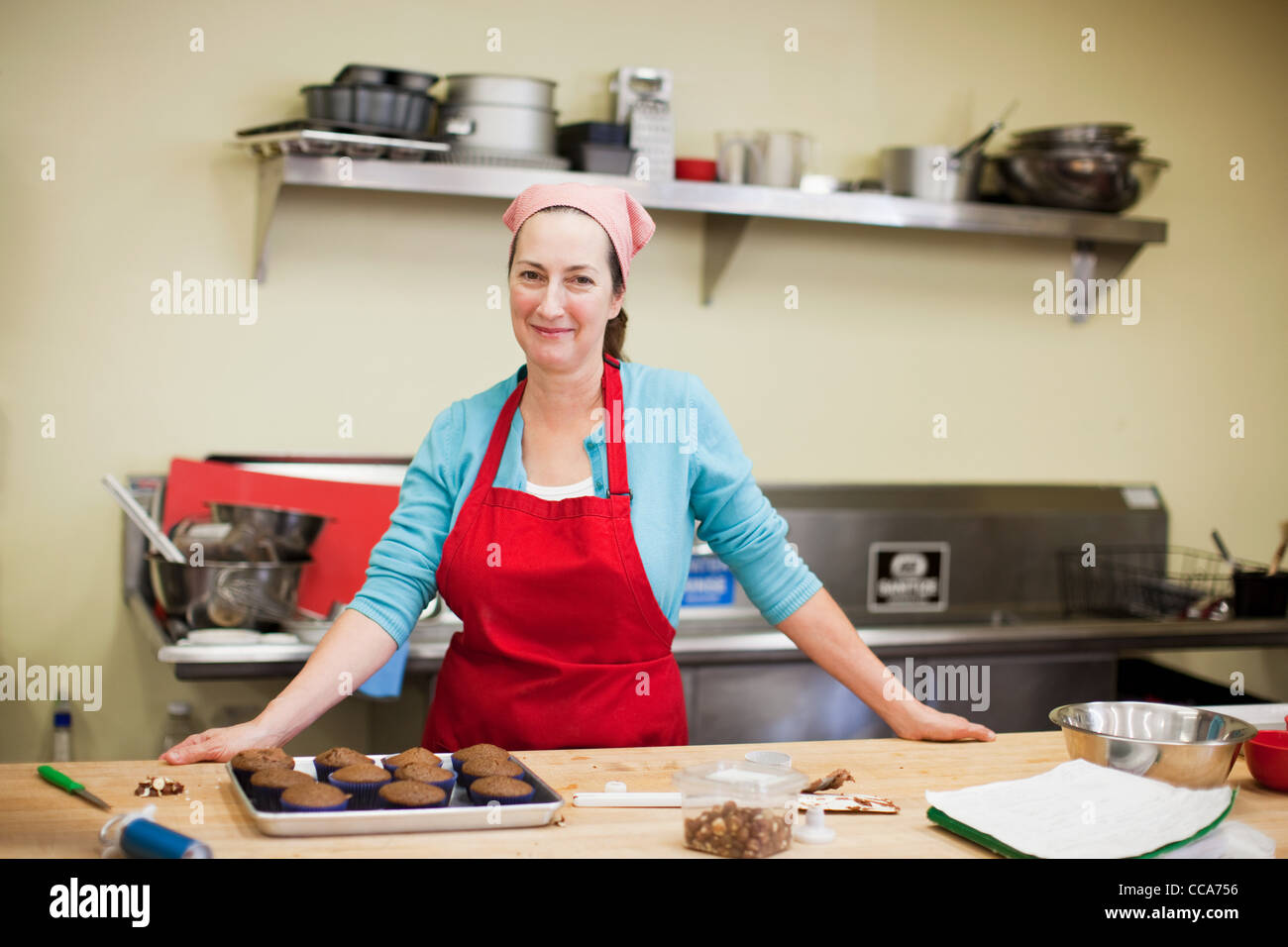 Portrait of woman working in bakery - Stock Image
