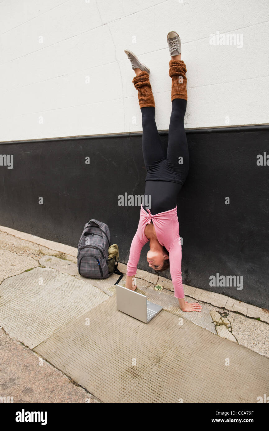 Woman performing handstand and using laptop on pavement - Stock Image