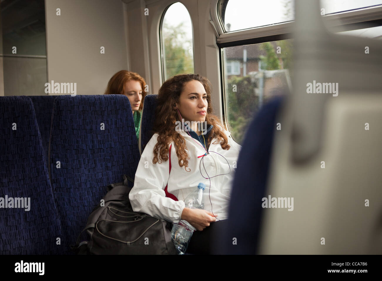 Two young women travelling on train - Stock Image