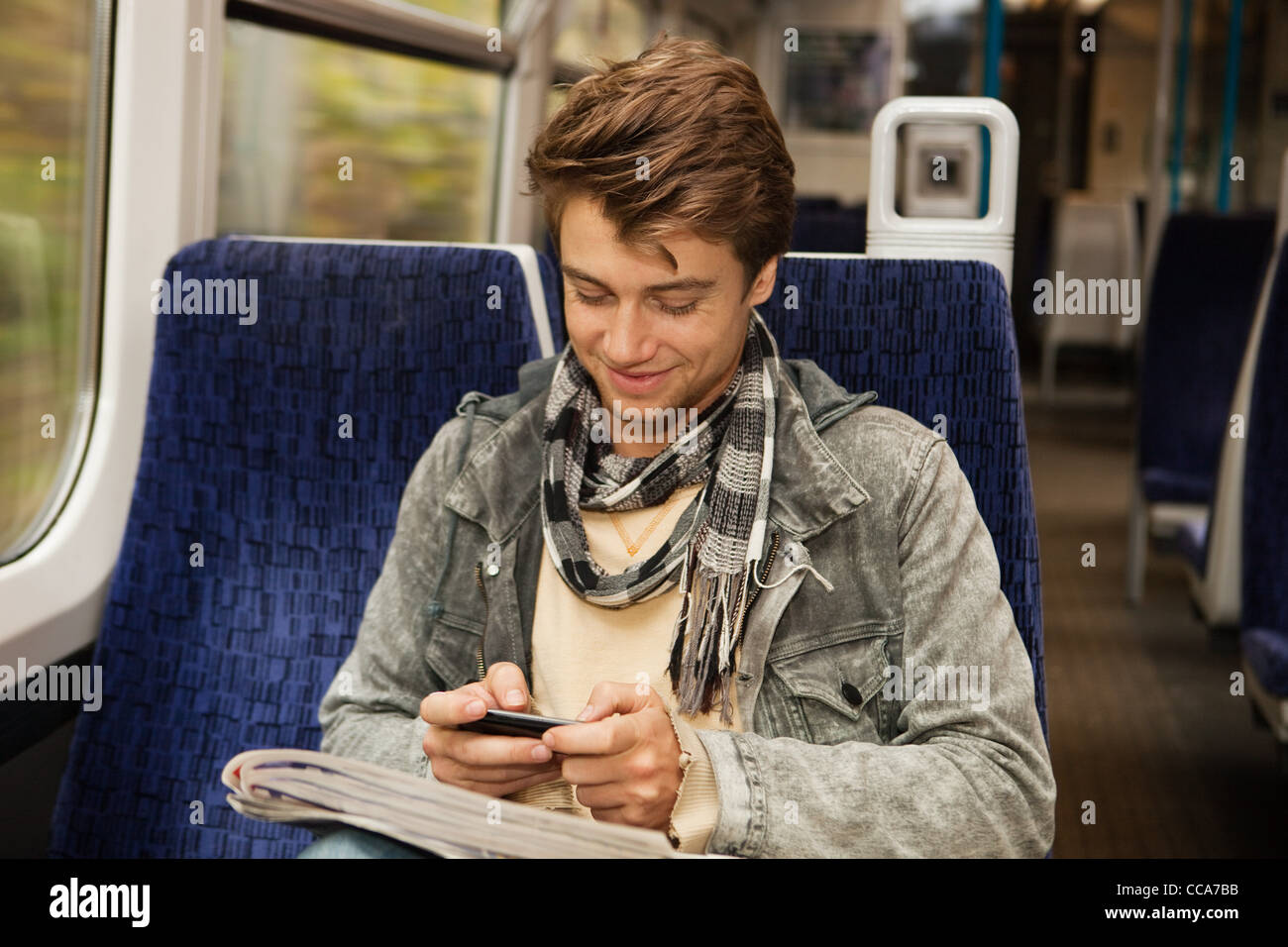 Young man travelling on train using cellphone - Stock Image