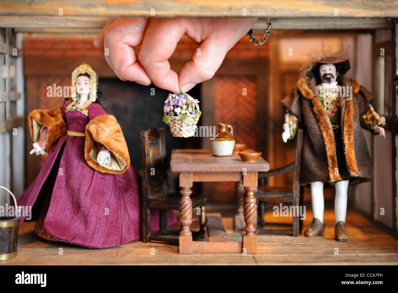 Kit Meggitt arranges items in her Tudor Aristocrats Solar Room displayed at 'Miniatura' - the dolls house - Stock Image