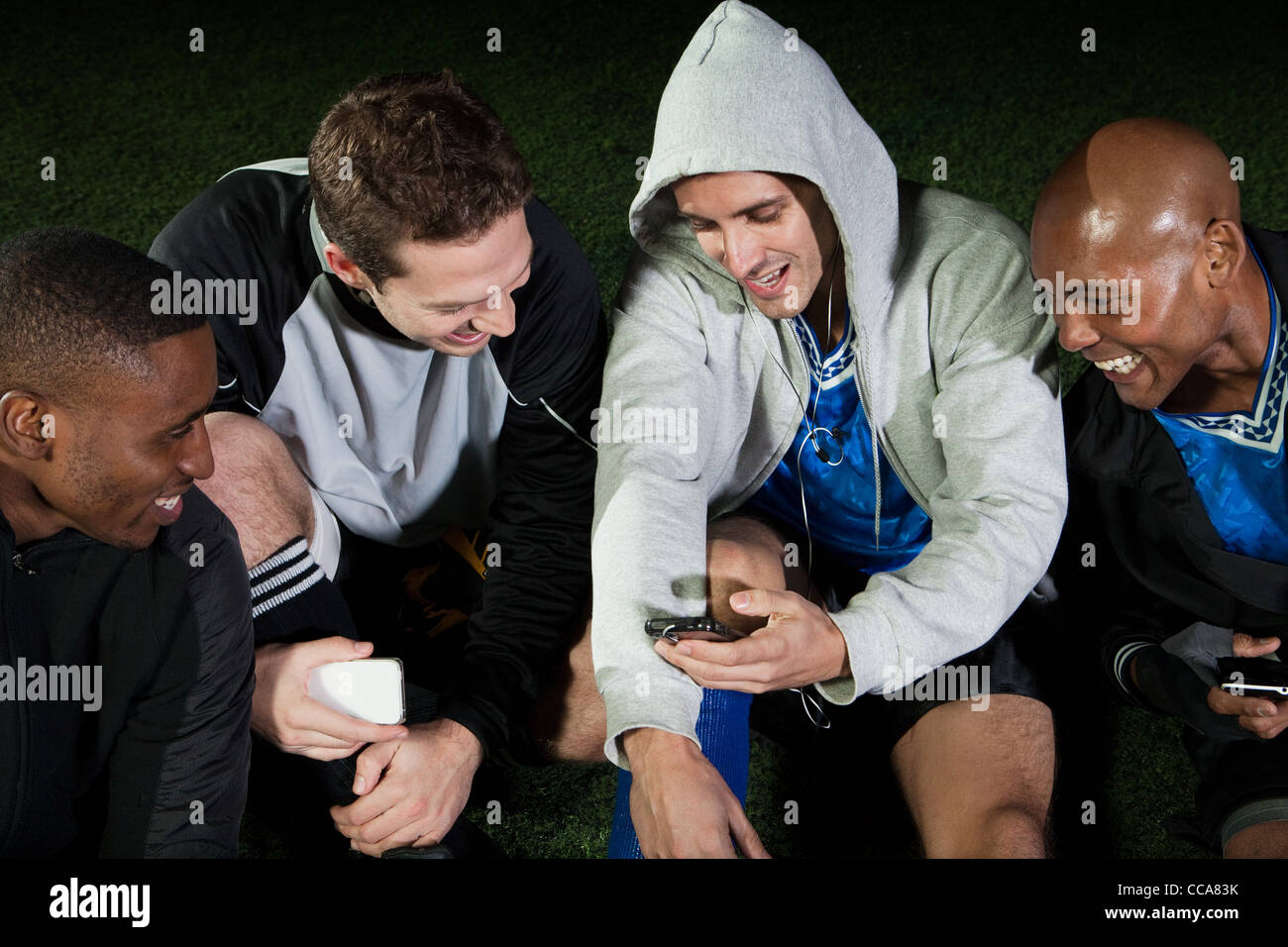 Soccer players looking at cellphone on pitch - Stock Image