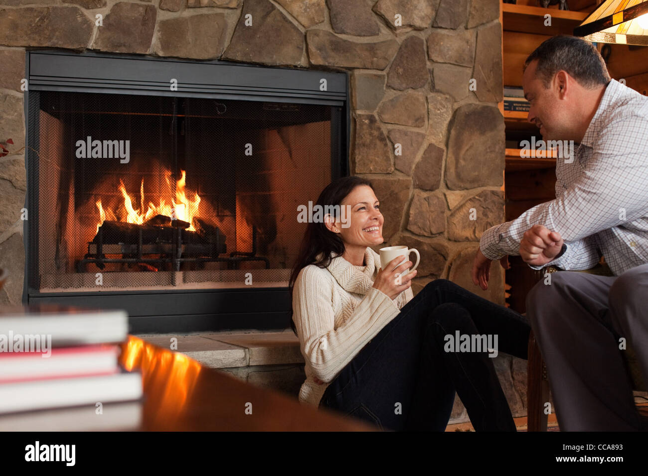 Mature couple relaxing by fireplace - Stock Image