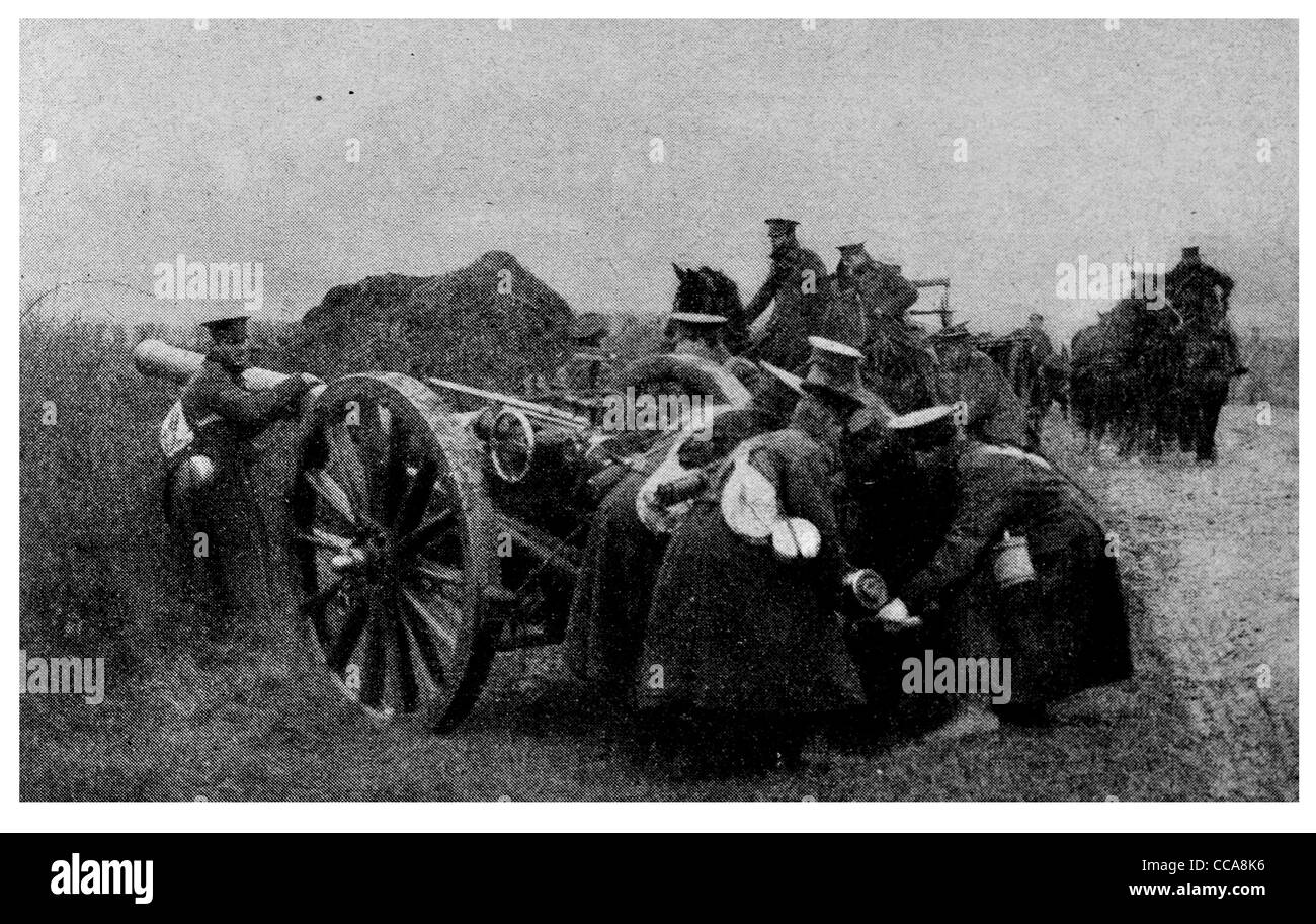 1915 French 4.7 inch Gun artillery cannon gunner gunners loading breach hidden howitzer aiming aim countryside road - Stock Image