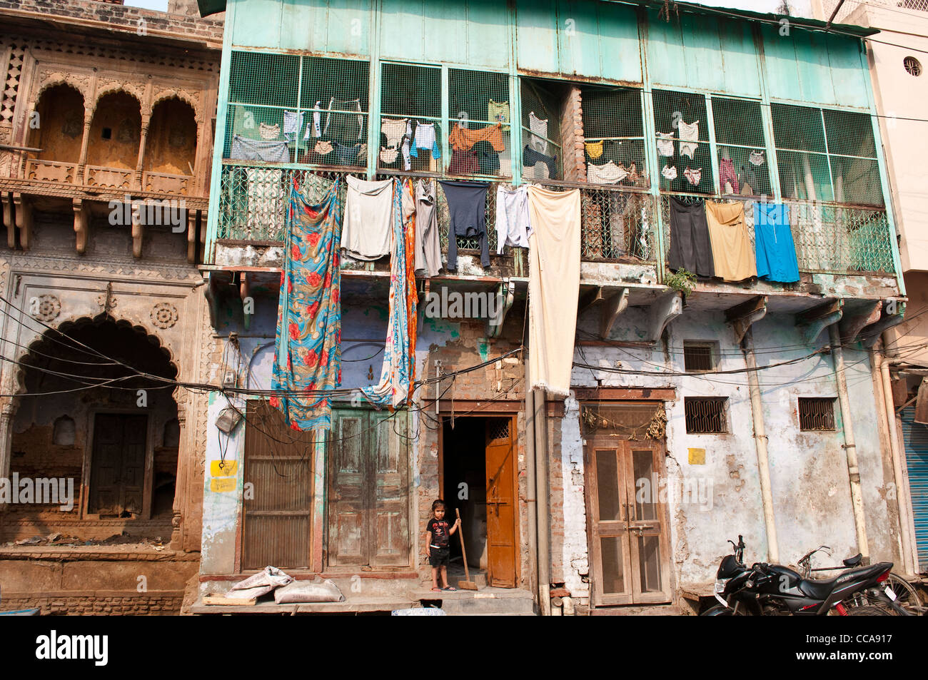 Little girl with a broom in front of a house with laundry drying, Vrindavan, Uttar Pradesh, India - Stock Image