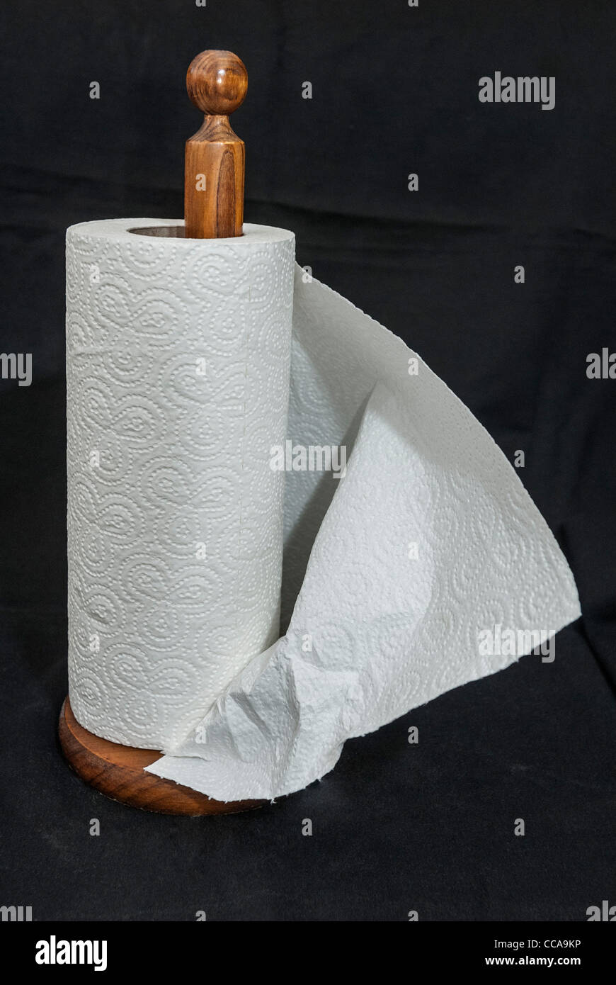 A roll of kitchen absorbent paper on a wooden holder. Stock Photo