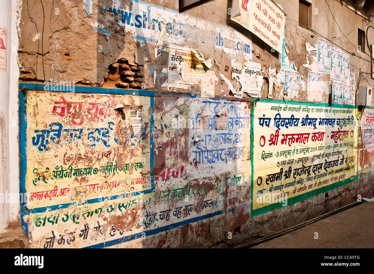 Wall covered with advertisements, Vrindavan, Uttar Pradesh, India - Stock Image