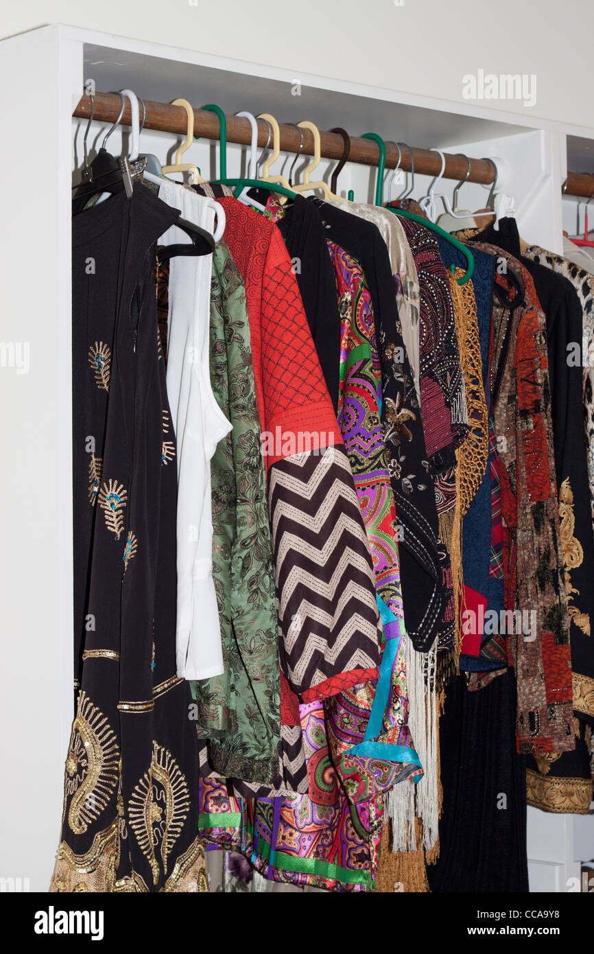 Clothes hanging in a closet - Stock Image
