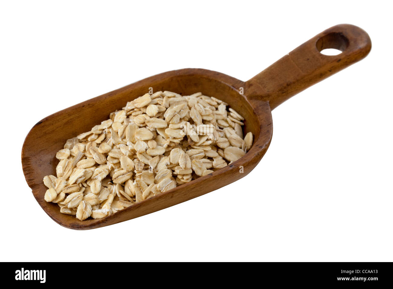 rolled oats on a rustic wooden scoop isolated on white - Stock Image