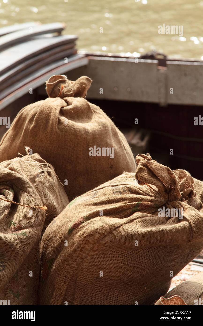 Jute sacks waiting to be loaded onto a docked barge - Stock Image