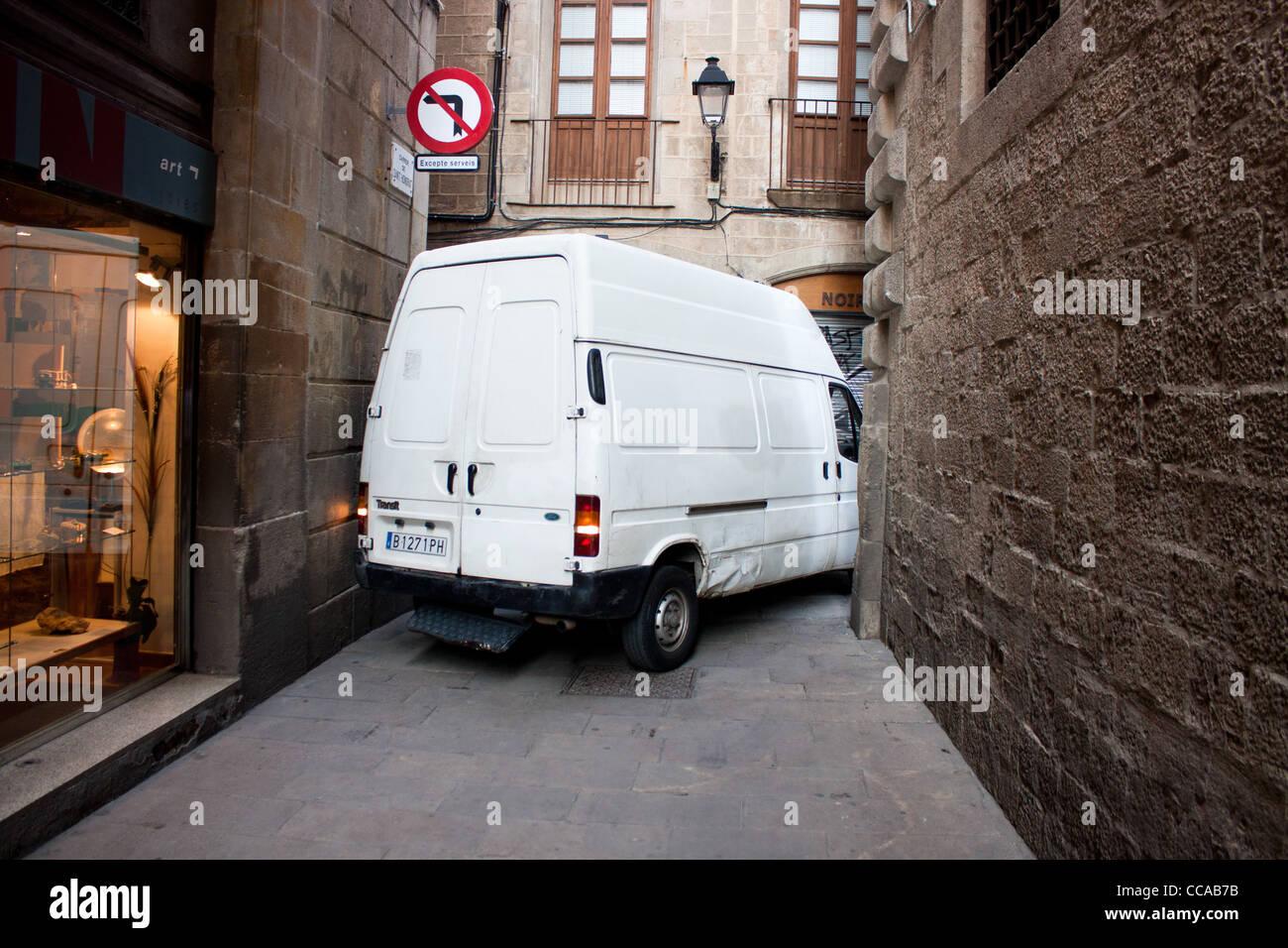 White panel truck stuck in narrow street in Barcelona Stock Photo