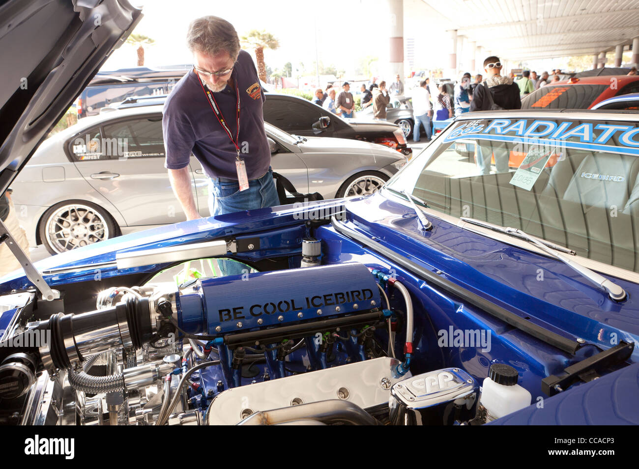 A car enthusiast inspecting a hot rod engine at car show - Stock Image