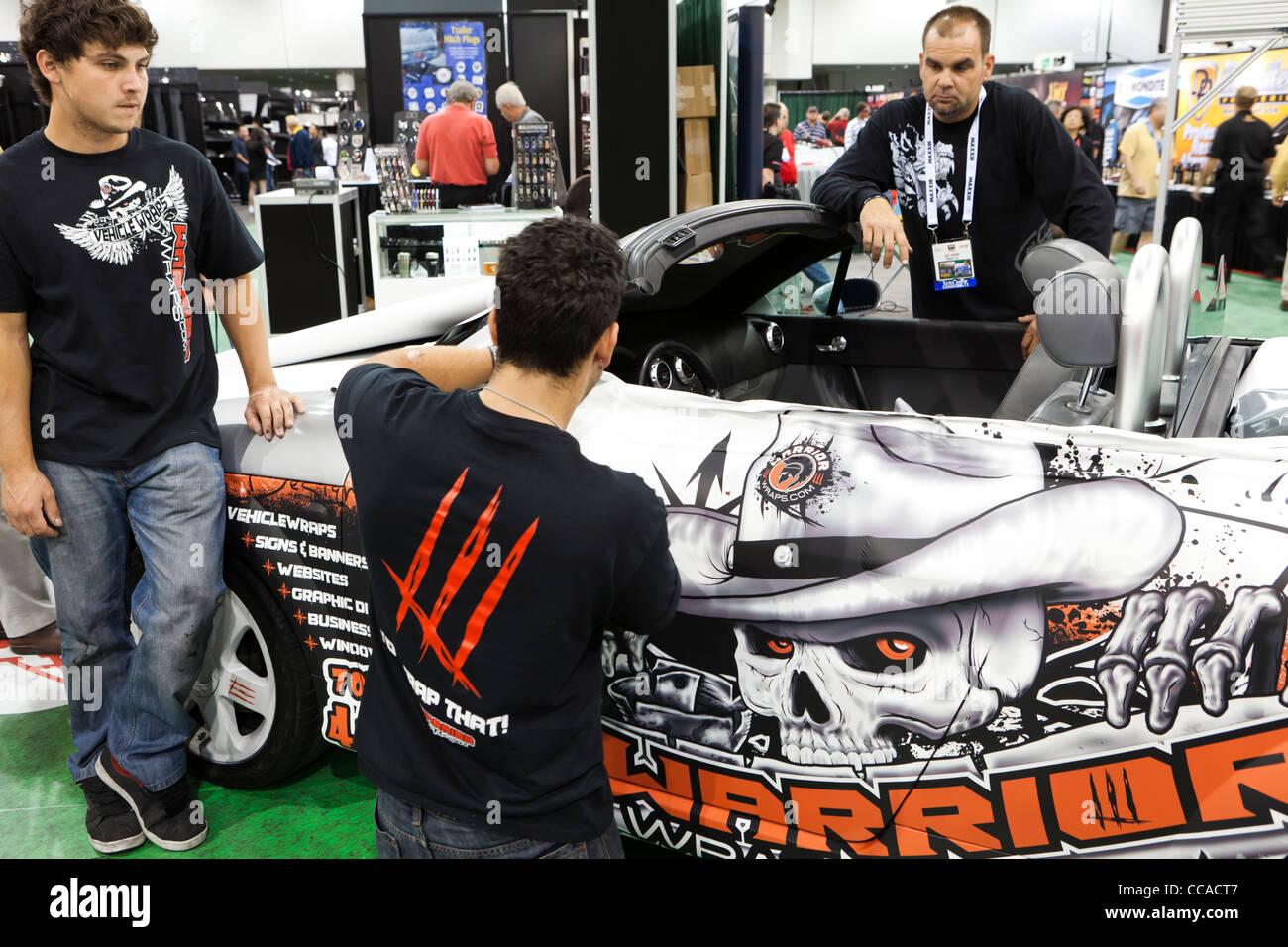 Technicians applying decorative auto body vinyl film - Stock Image
