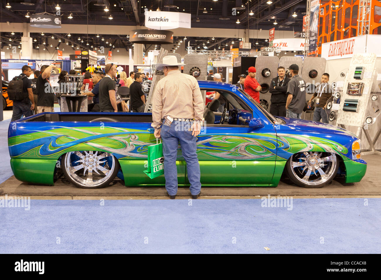 A man viewing a low rider pick-up truck rebuild on display at car show - Stock Image