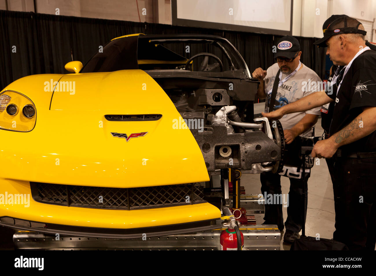 Two mechanics inspecting a cutaway model of car - Stock Image