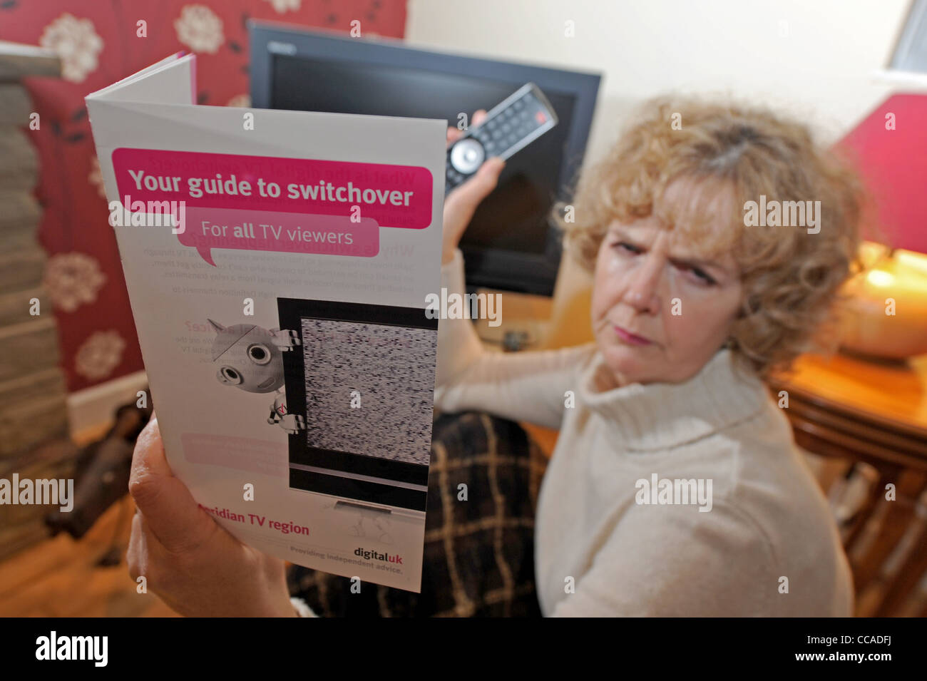Middle aged woman reads the instruction leaflet for the Meridian TV area from digitaluk on the digital switchover - Stock Image