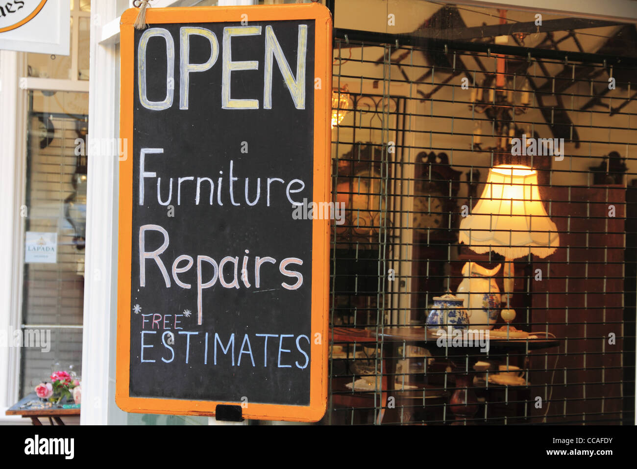 Sign advertising furniture repair repairs and free estimates in an antiques antique shop window. - Stock Image