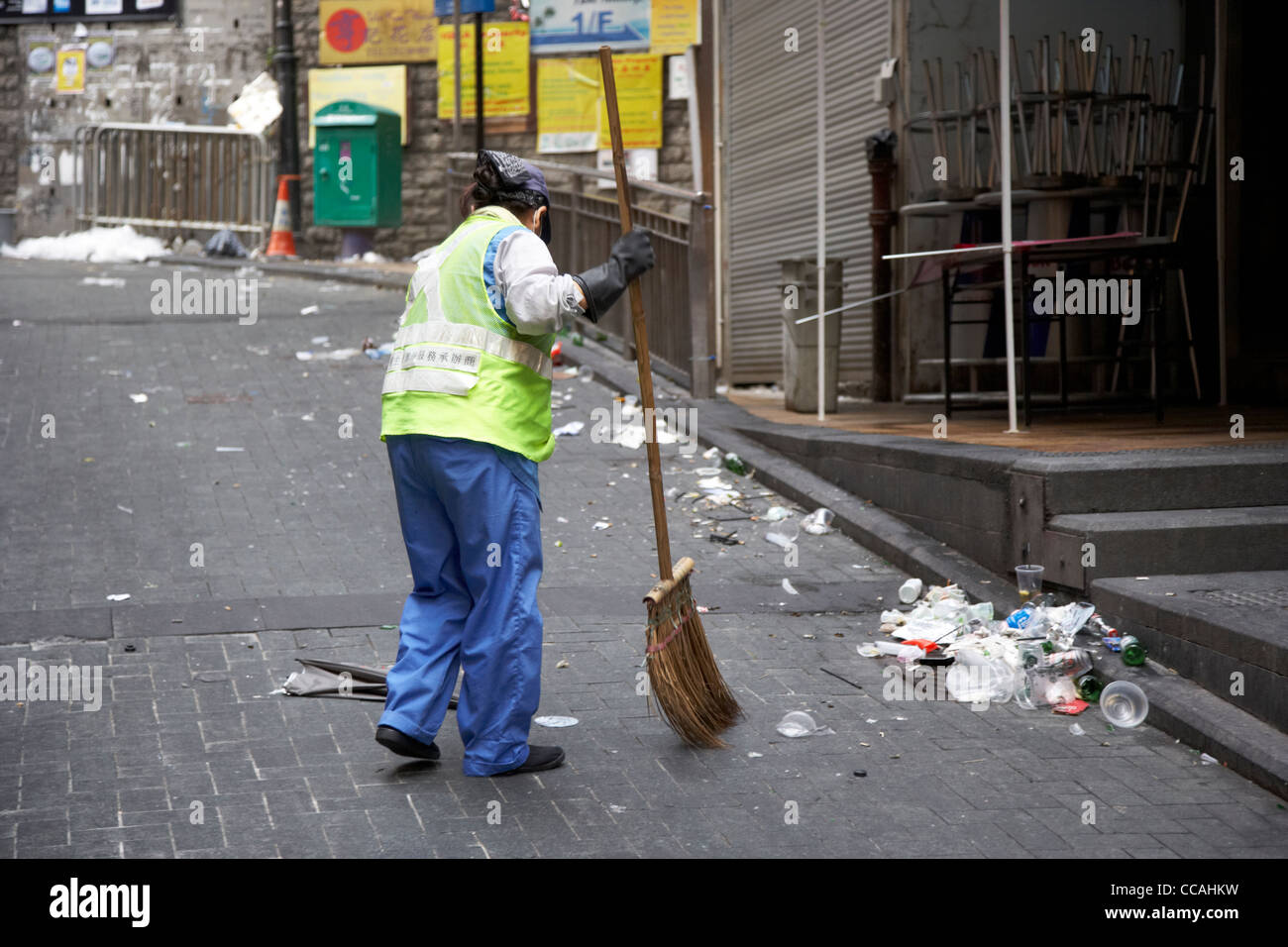 female street cleaner brushing streets with broom early morning in lan kwai fong hong kong hksar china asia - Stock Image
