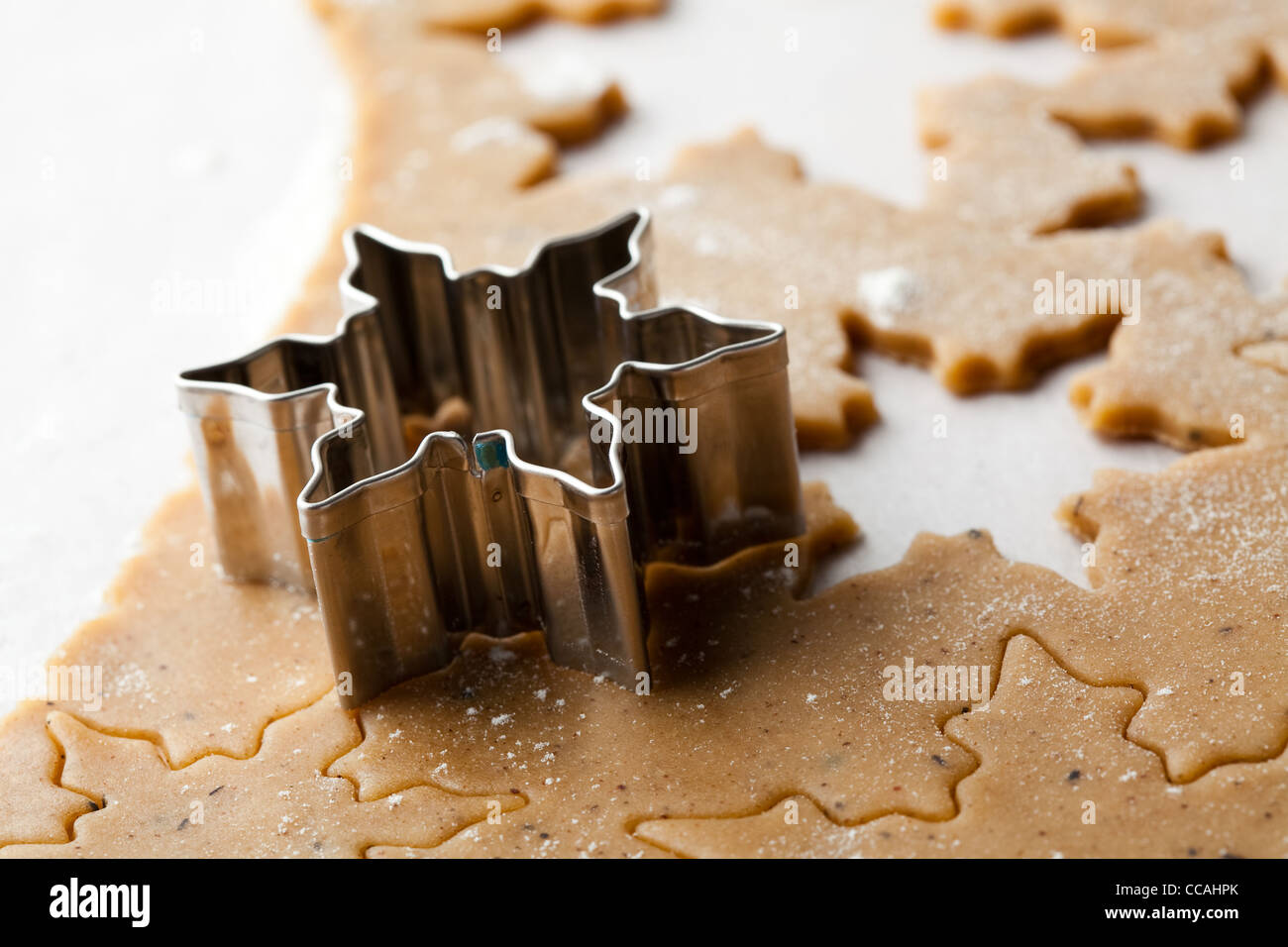 Making gingerbread cookies for Christmas. Gingerbread dough with star shapes and a cutter. - Stock Image