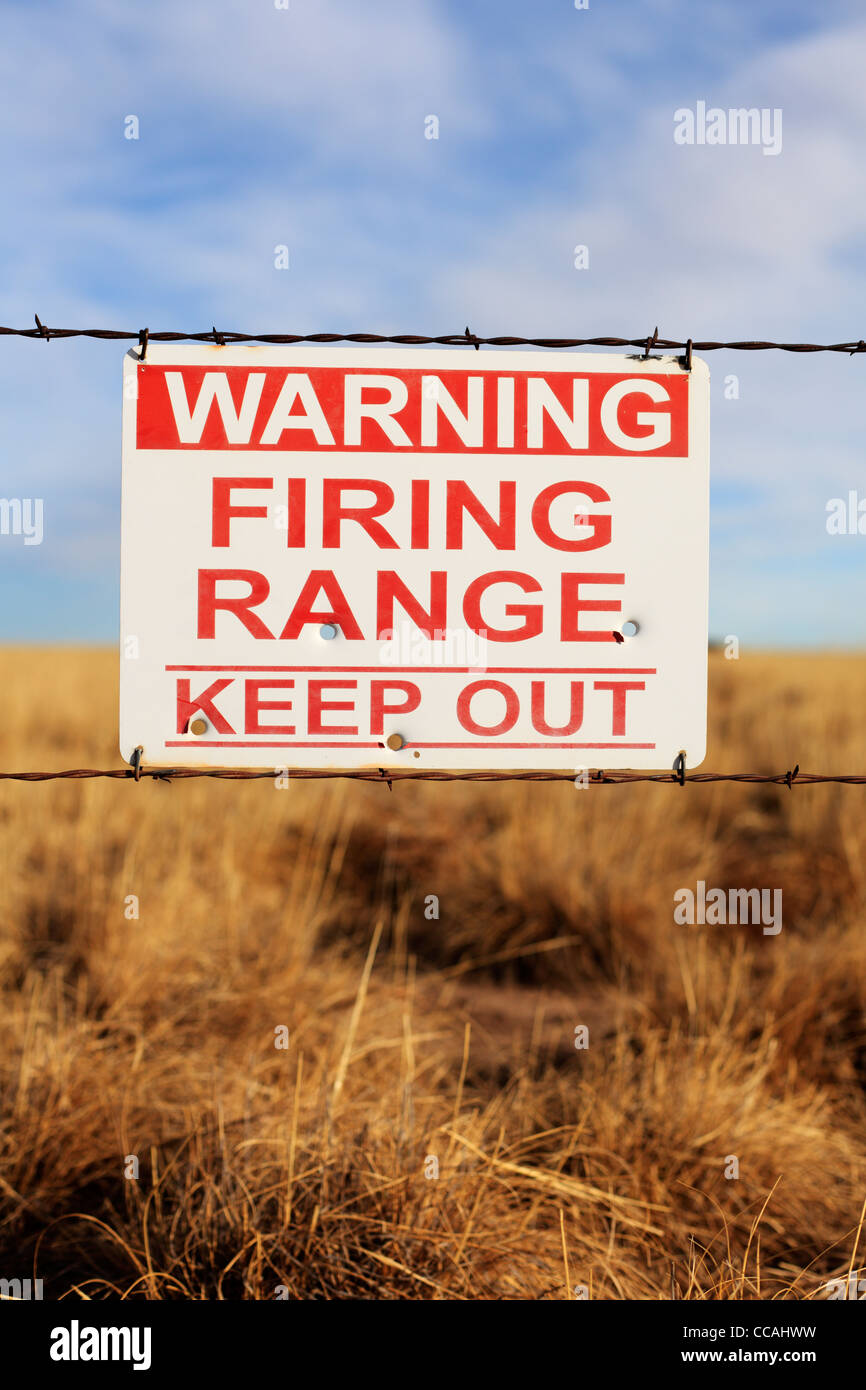 Warning Firing Range Keep Out sign hanging on a barbed wire fence. - Stock Image