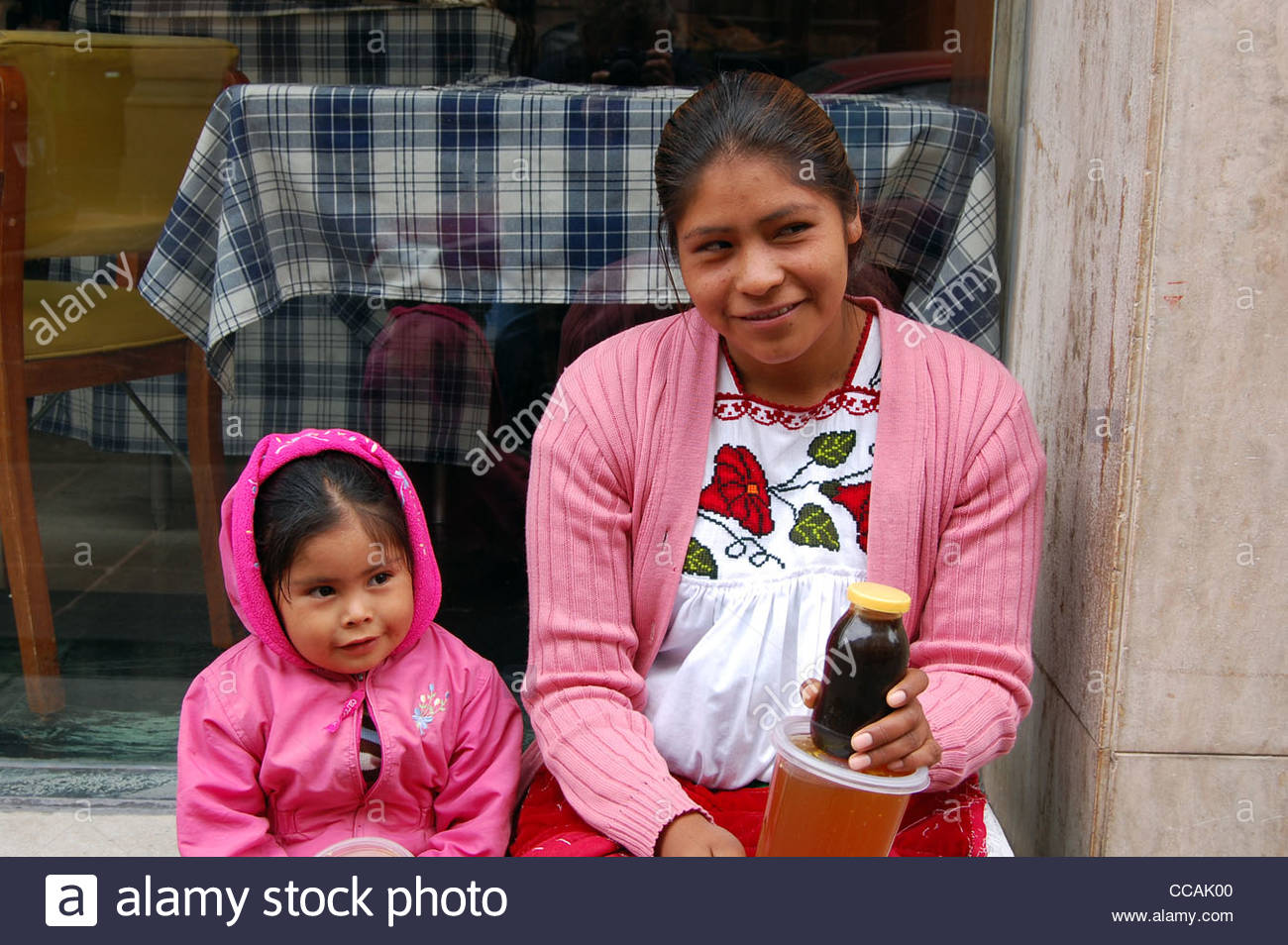 Street scene Mexican mother and daughter selling honey to passerby looking at camera. Social issues single parenting - Stock Image