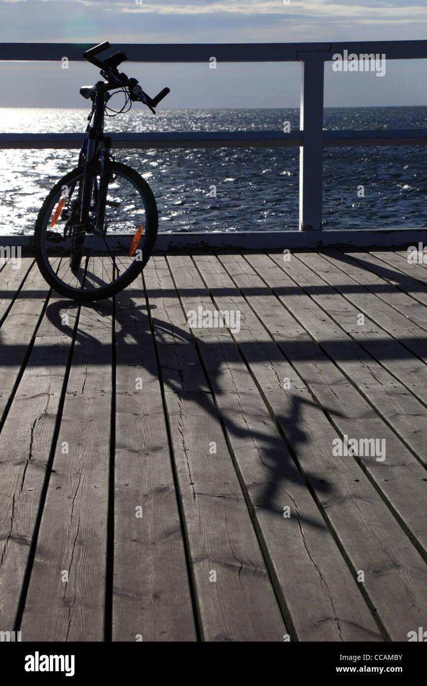 bicycle bicycling bike biking black cycle evening horizon jetty landscape mountainbike mountainbiking murk nature - Stock Image