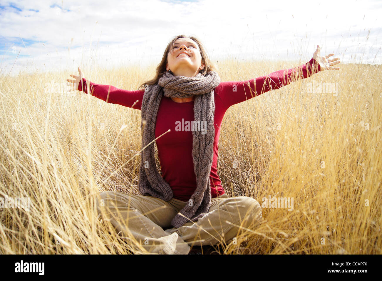 Beautiful young woman spreading her hands with joy and happiness while sitting in the long grass of autumn field - Stock Image