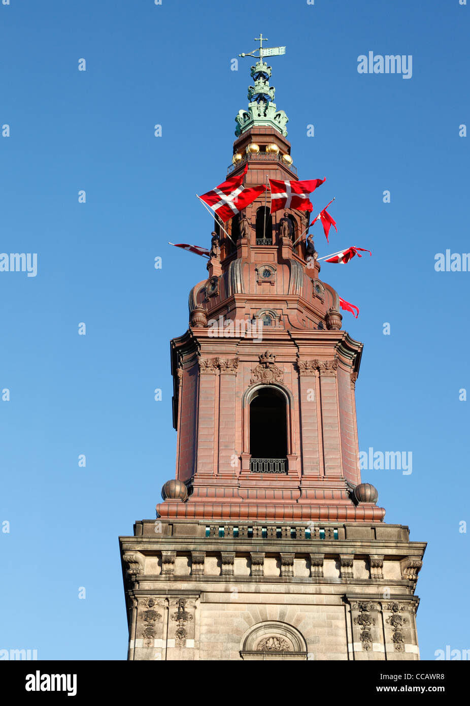 Danish flags in the tower windows of Christiansborg Palace, the parliament building in Copenhagen, Denmark, in celebration. Stock Photo