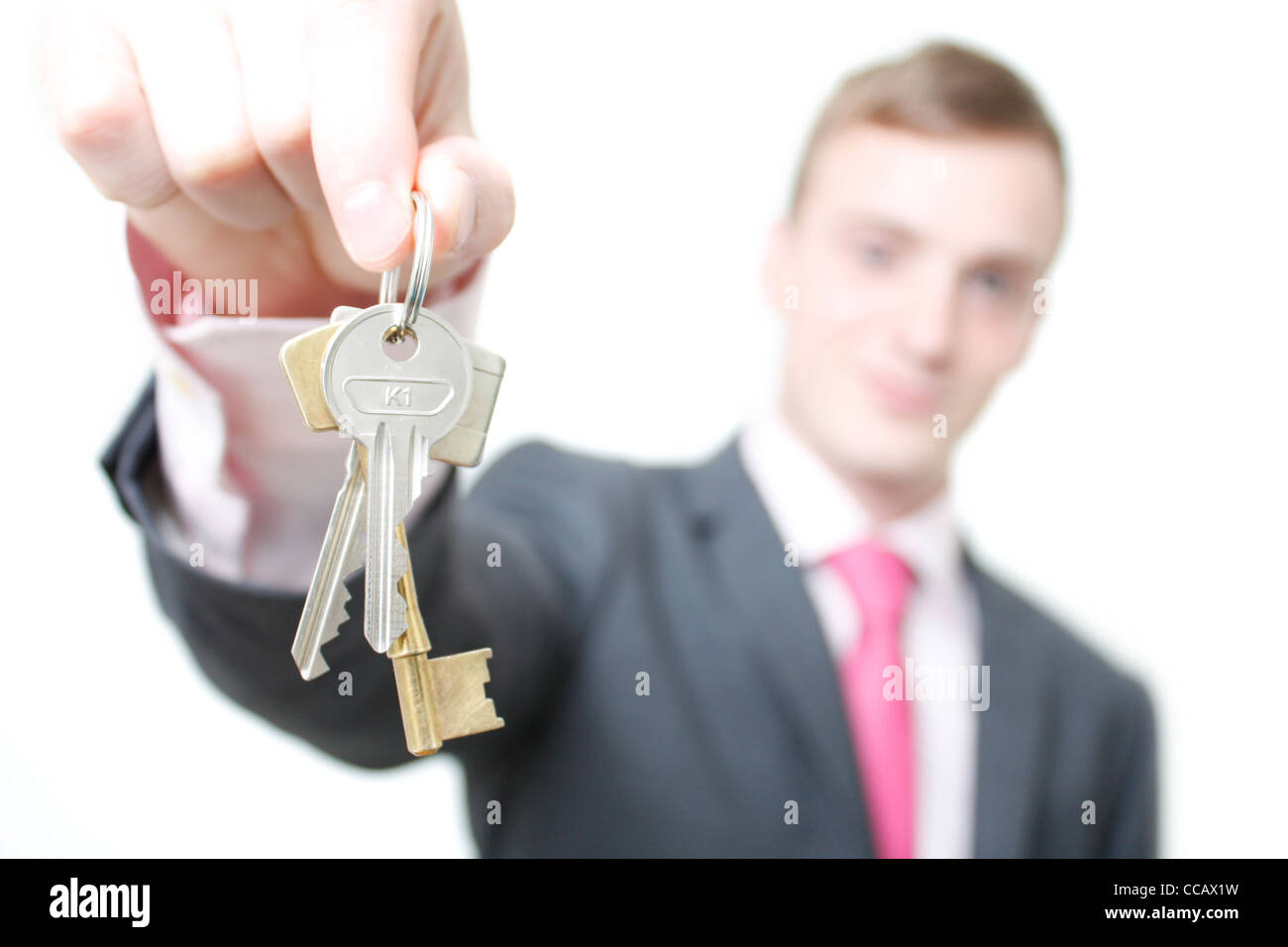 A business man giving you the keys to a home - Stock Image