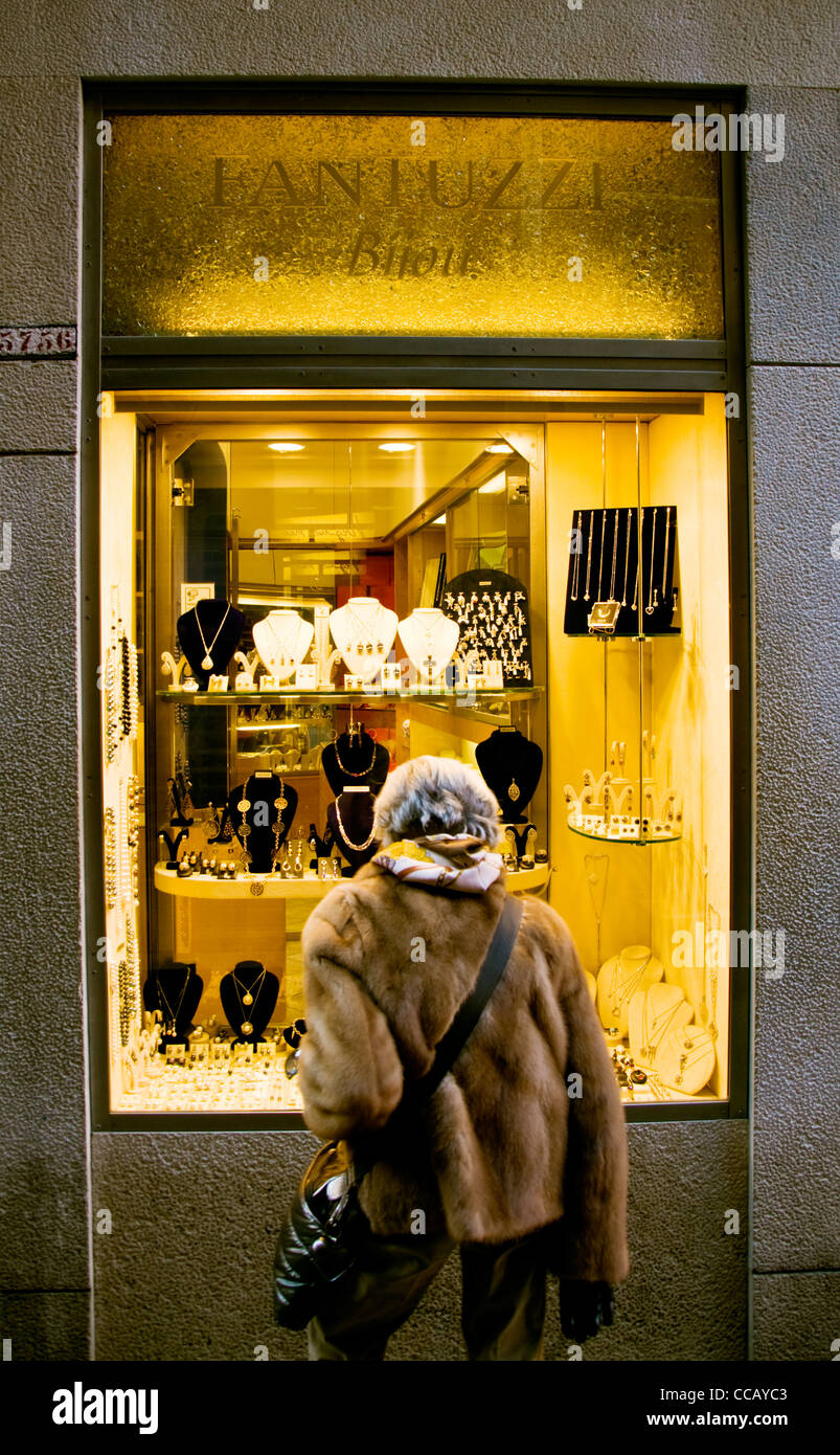 Woman wearing a fur coat looking into a jewellery shop window - Stock Image