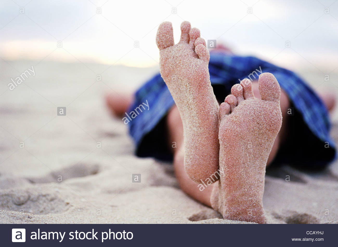 Sandy feet of man laying on beach with legs crossed - Stock Image