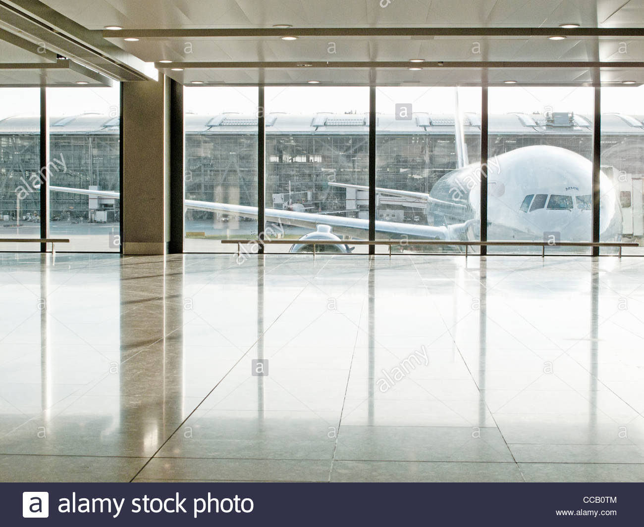 Airplane seen through window in airport terminal - Stock Image