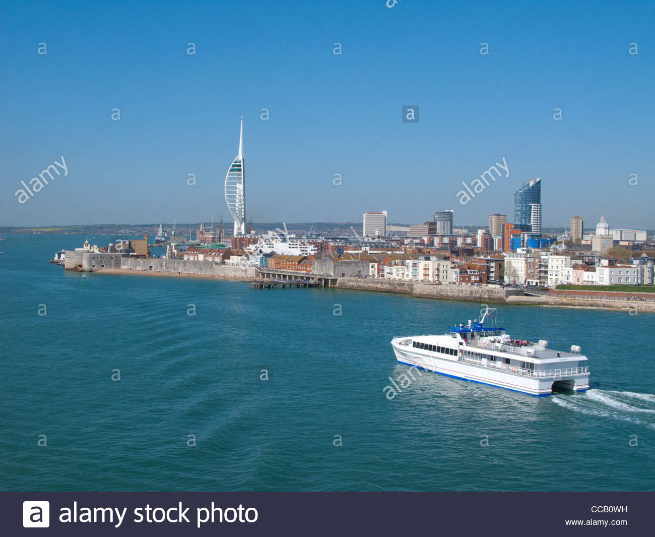 Ferry boating past cityscape of Portsmouth with modern spire in background - Stock Image
