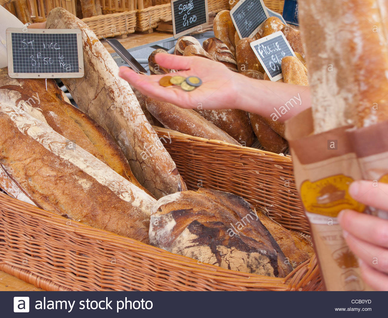 Woman holding coins buying rustic loaf of bread from market - Stock Image