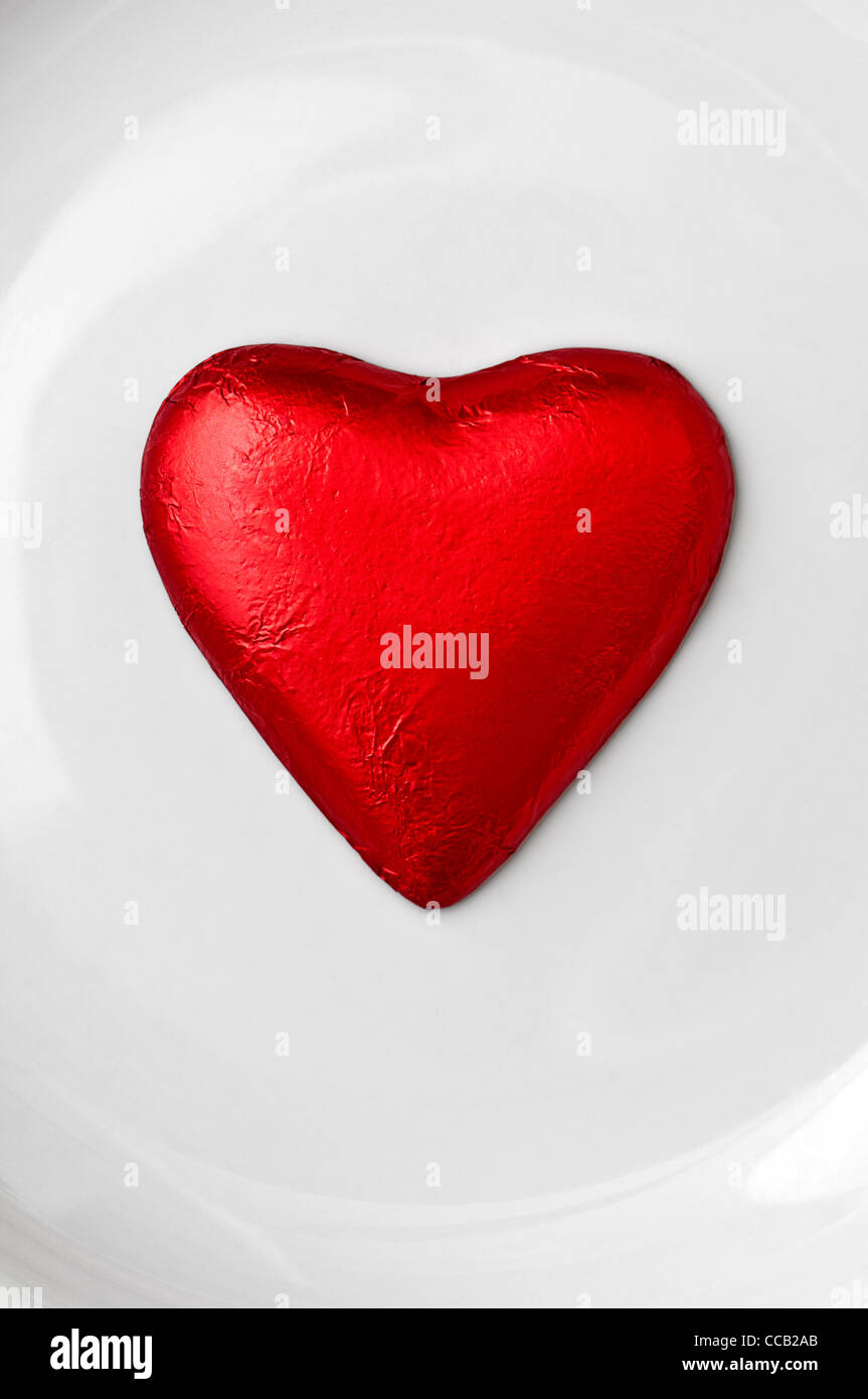 Red foil wrapped chocolate heart on a white plate background - Stock Image